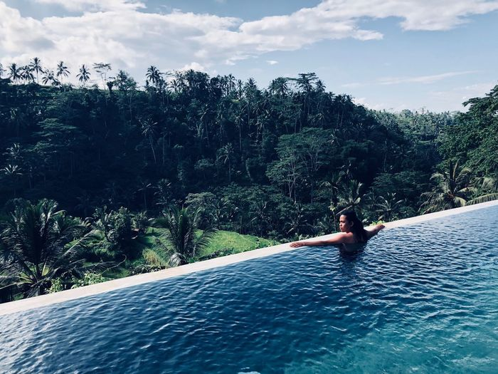 Shirtless man swimming in infinity pool against forest