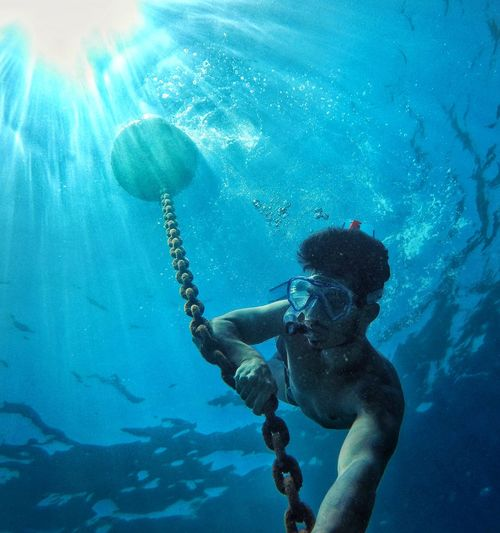 Low angle view of shirtless man holding chain in sea