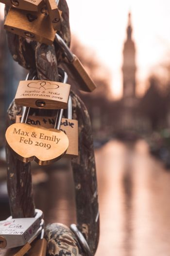Love locks attached to a bridge in Amsterdam with churchtower in the background Committment Amsterdam Lovelocks Canal Church Tower Architecture Text Communication Focus On Foreground City Padlock Built Structure Lock Positive Emotion Hanging Travel Destinations Close-up Travel Love