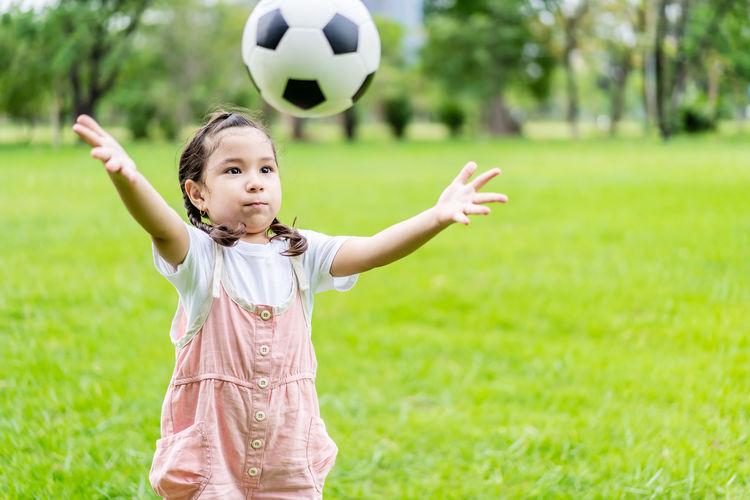 Full length of girl holding ball on field