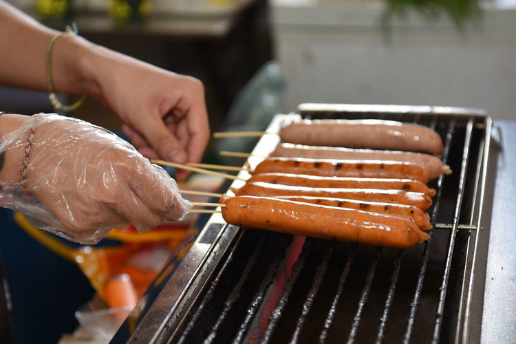 Cropped Hand Of Person Preparing Sausages On Barbecue Grill