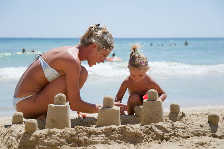 Adult Beach Blond Castle Caucasian Child Childhood Children Coast Creative Daughter Exotic Family Female Fun Girl Happy Holiday Infant Joy Kid Lifestyle Little Loving Making Mom Mother Ocean Parent People Playing Sand Sand Tower Sandcastle Sea Seaside Smile Smiling Summer Sunny Swimsuit Together Togetherness Toys Tropical Turquoise Vacation Water Woman Young