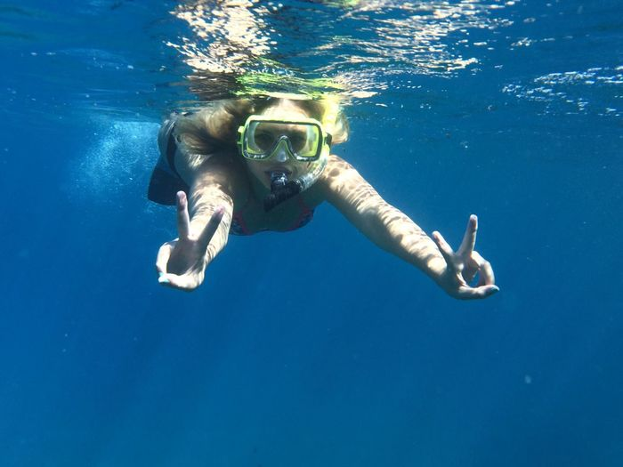 Portrait of young woman showing victory sign while swimming in sea