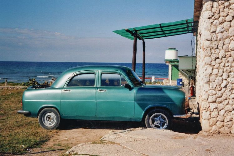 Vintage car by sea against sky