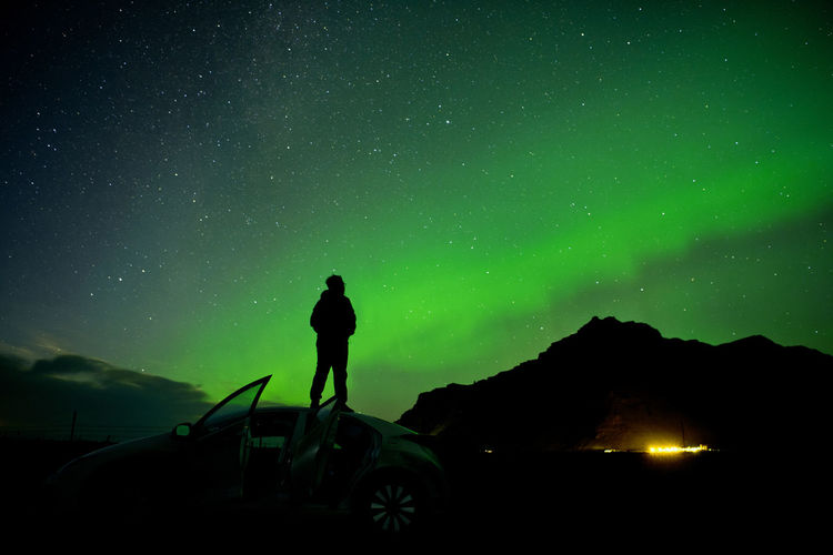 Silhouette Man Standing On Car Roof Against Aurora Borealis