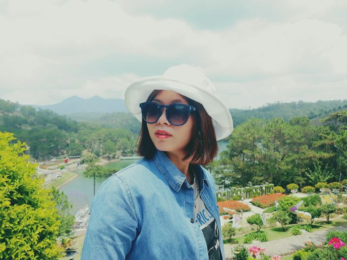Young woman wearing sun hat while standing on mountain against sky