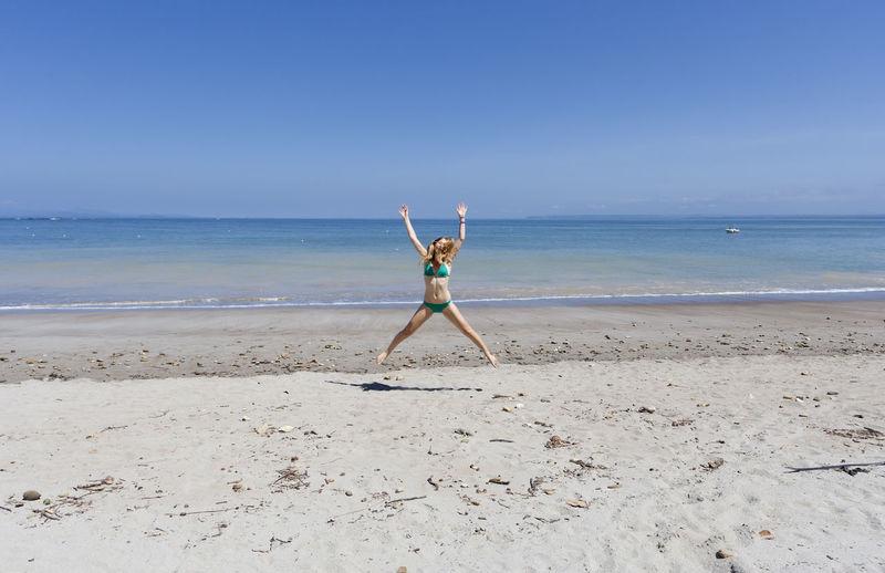Full length of woman in bikini jumping at beach against clear blue sky