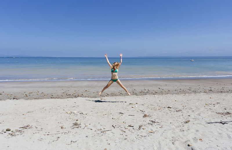 Playful mid adult woman jumping at beach against blue sky