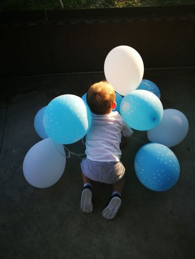 Rear view full length of boy playing with balloons on floor