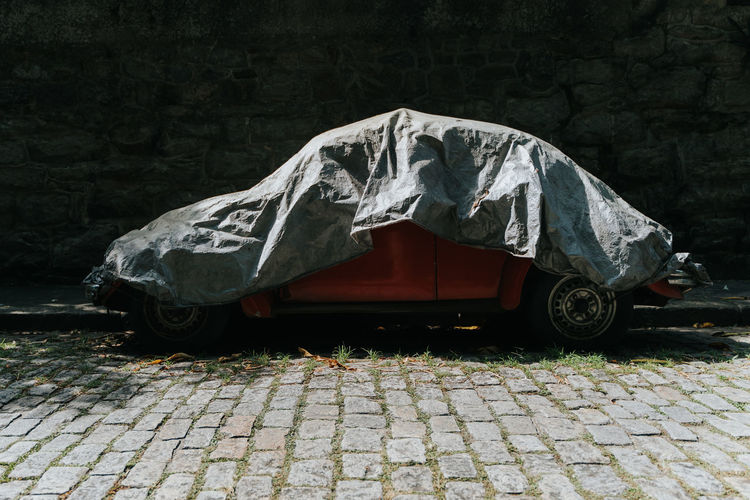 Car with cover on cobblestone street