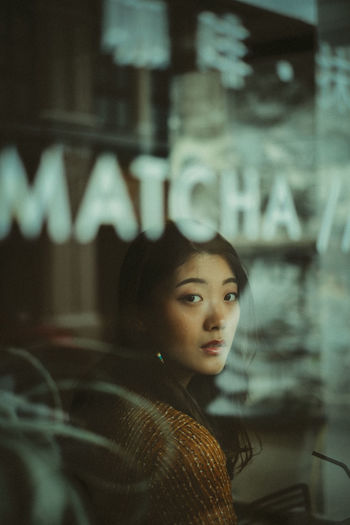 Portrait of young woman sitting in cafe seen through window