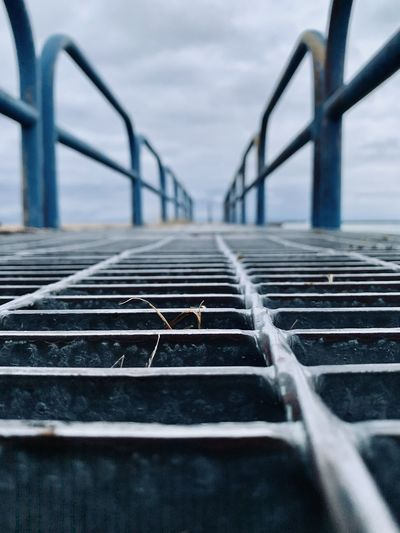 Close-up of metal grate against sky