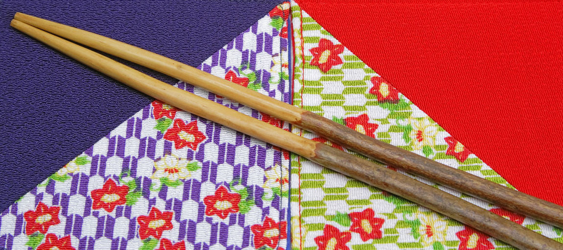 Image of two chopsticks made by cherry tree wood on two piece of specific Japanese fabric. Multi Colored No People Pattern Close-up Still Life Art And Craft Wood - Material Studio Shot Tablecloth Textile Floral Pattern Colored Background Directly Above Chopsticks Wooden Chopsticks