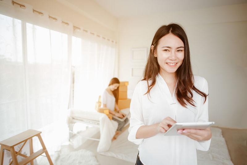 Portrait of smiling woman using digital tablet