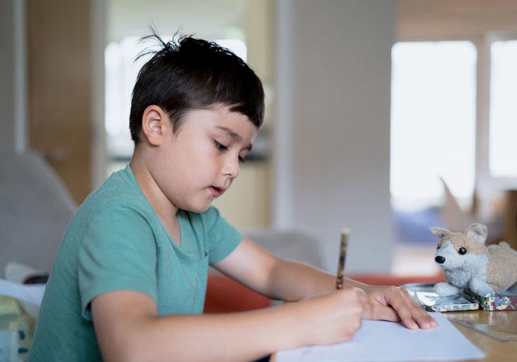 Boy looking at table at home