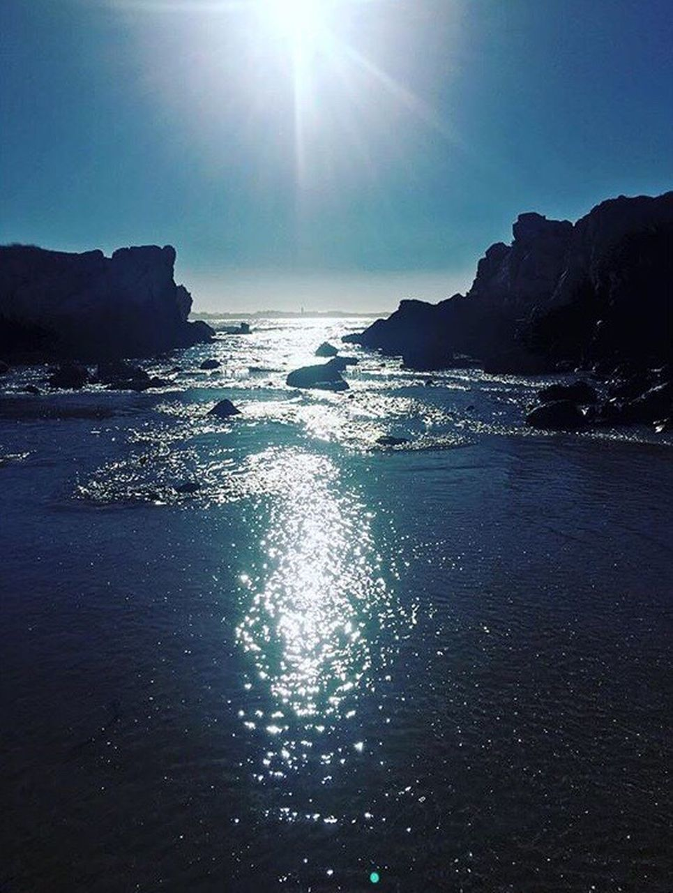 sea, sun, sunlight, scenics, nature, beauty in nature, lens flare, sunbeam, water, tranquility, sky, horizon over water, no people, rock - object, beach, outdoors, tranquil scene, travel destinations, clear sky, day, blue, wave
