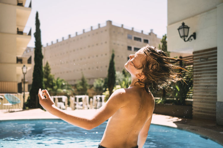 Portrait of young woman standing by swimming pool