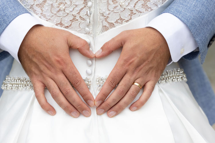 Midsection of woman making heart shape with hands