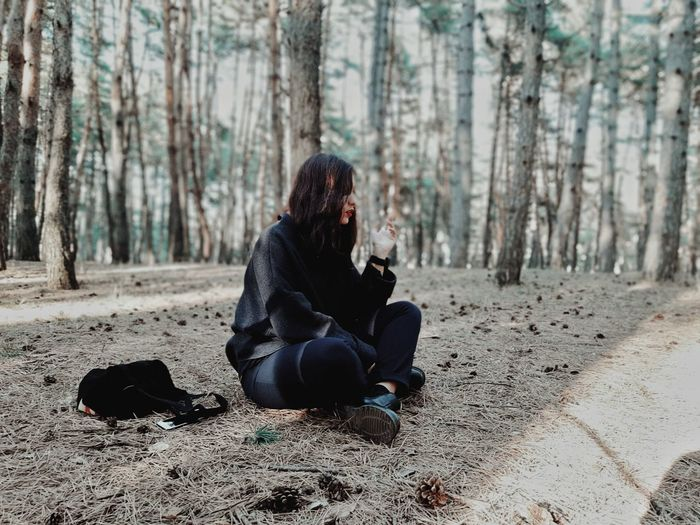 Full length of woman sitting in forest