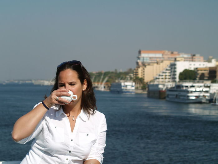 Woman Drinking Coffee By River Against Sky