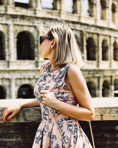 Woman standing against coliseum