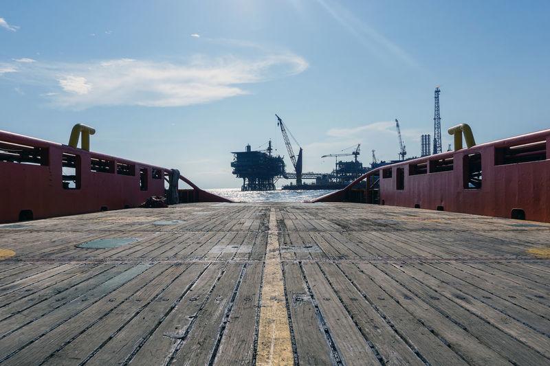 Footpath by pier against sky