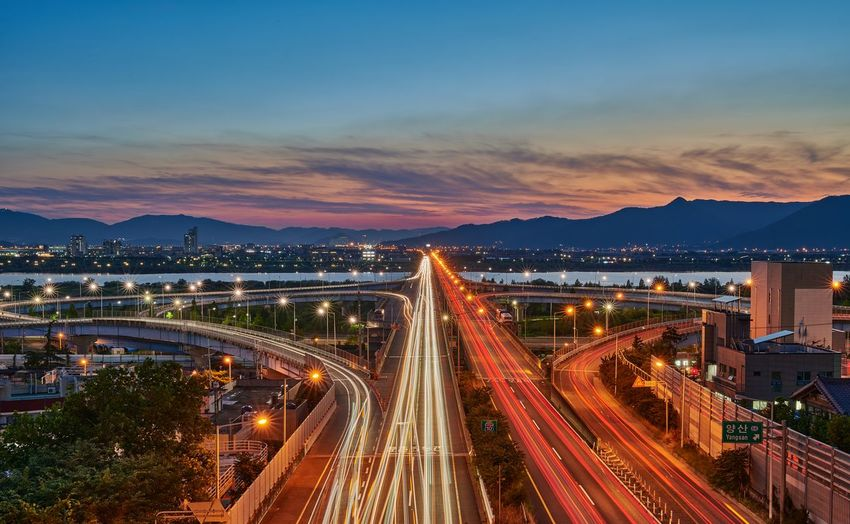 High angle view of light trails on road against sky during sunset