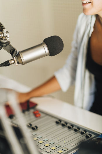 Microphone in podcasting studio - female announcer recording podcast