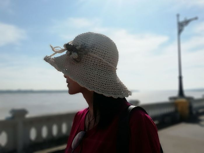 Close-up of woman wearing hat against sea and sky