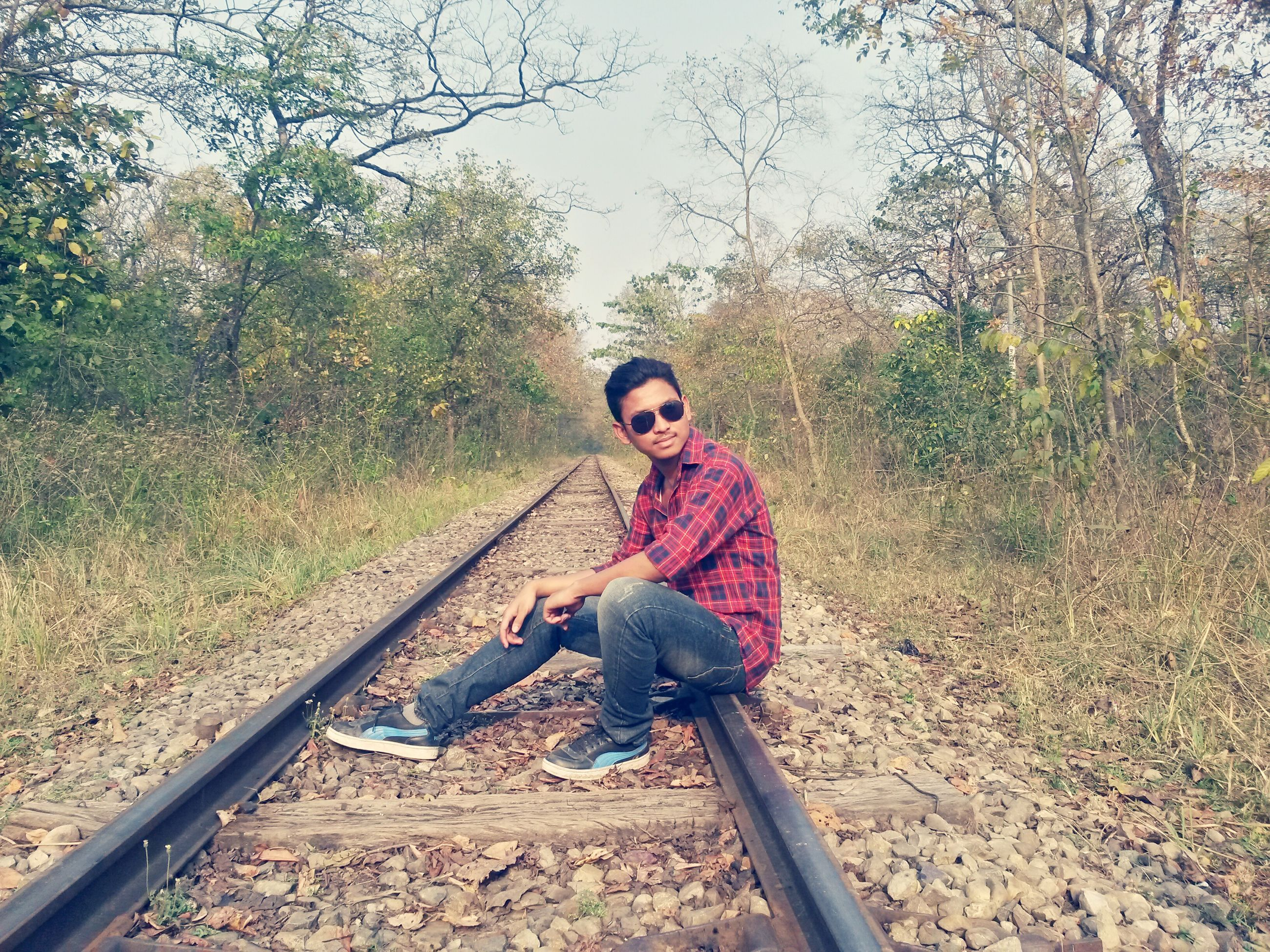 person, casual clothing, lifestyles, full length, leisure activity, railroad track, tree, transportation, young adult, portrait, looking at camera, front view, standing, smiling, rail transportation, day, holding, nature