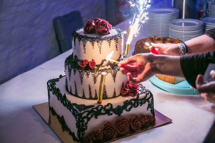 Cropped hands of women igniting candles on cake