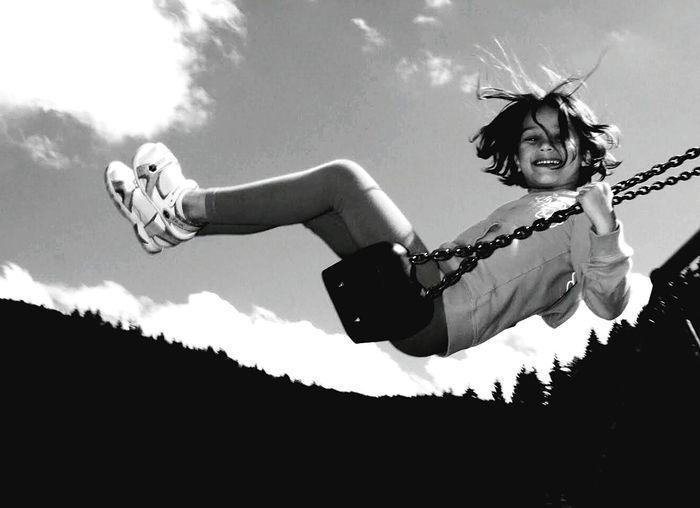 Portrait of happy girl swinging against sky