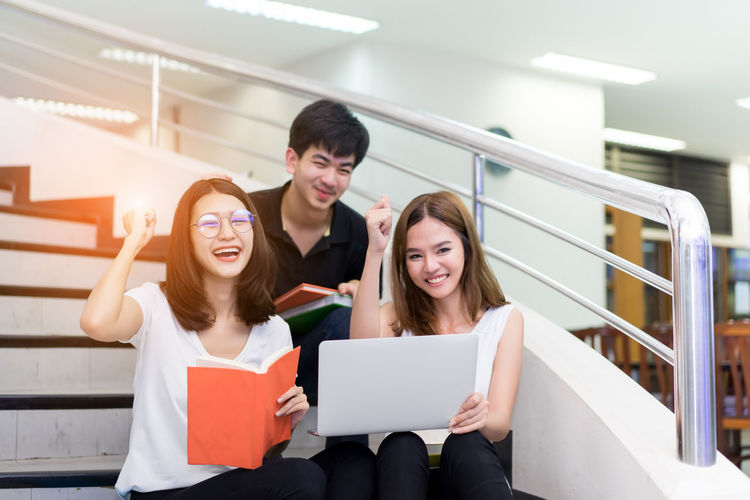 Portrait of friends studying while sitting on steps in college