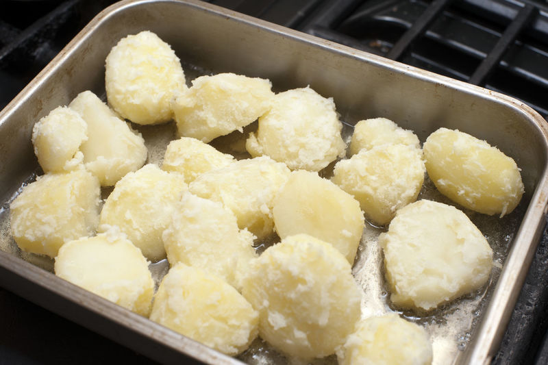 Preparing roast potatoes by par boiling them and placing them in an oven dish with oil to roast and crisp up Cooking Cooking Duck Fat Fat Flour Floured Surface Food Food And Drink Potato Potatoes Preparation  Preparation  Preparing Preparing Food Roast Roasting Pan Roasting Tin Roasting Tray