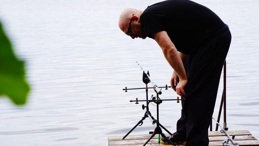 Bald man standing by lake