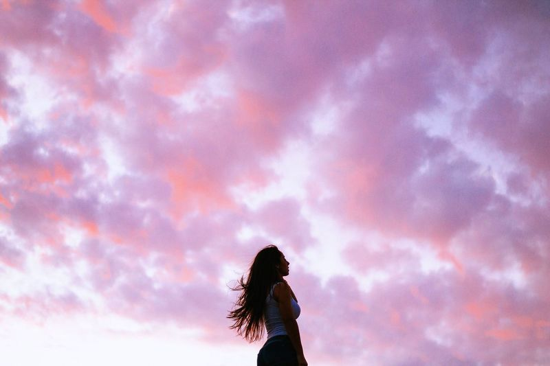Low Angle View Of Woman Standing Against Cloudy Sky During Sunset