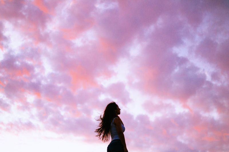 Low angle view of silhouette woman standing against sky