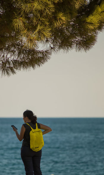 Back View Paint The Town Yellow Yellow Back-Pack Calm Seas Clear Sky Distant Horizons Horizon Over Water On The Beach One Person Outdoors Pine Trees Against The Sky Sea Young Women