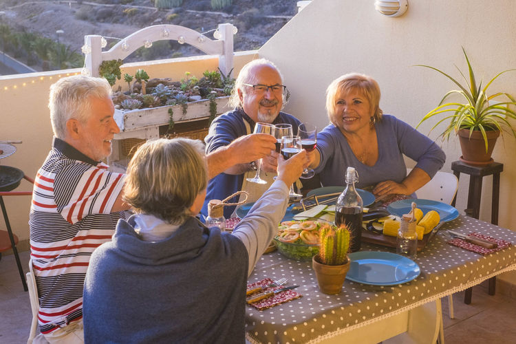 Senior Couples Toasting Drinks While Sitting At Dining Table