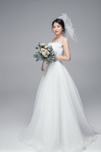 Portrait of bride with bouquet standing against gray background