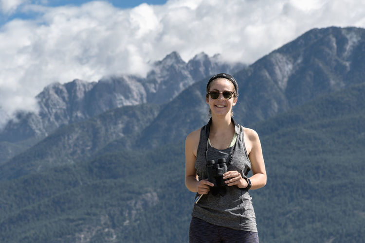 Young athletic woman hiking in the Canadian Rockies Sunglasses Mountain Smiling Fashion Mountain Range Front View Standing Young Adult Adult Portrait Scenics - Nature One Person Happiness Beauty In Nature Outdoors Casual Clothing Female Woman Athletic Hiking British Columbia Canada