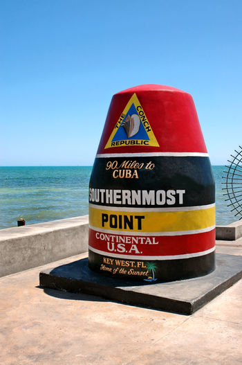 USA Southernmost Point Monument and Key West Tourist Attraction Cuba Distance Sign Key West Southernmost Point In The USA Tourist Attraction  Carabbean Clear Sky Conch Republic Distance Marker Florida Florida Keys Geographical Marker Horizon Over Water Local Landmark National Landmark No People Southern United States Southernmost Point Tourist Destination Travel Destinations Water