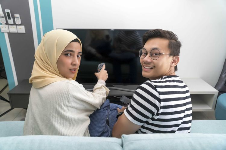Young Malay Couple at the Sofa watching tv together Two People Smiling Real People Young Adult Indoors  Sitting Casual Clothing Young Women Emotion Happiness Lifestyles Portrait Adult Young Men People Leisure Activity Looking At Camera Furniture Holding