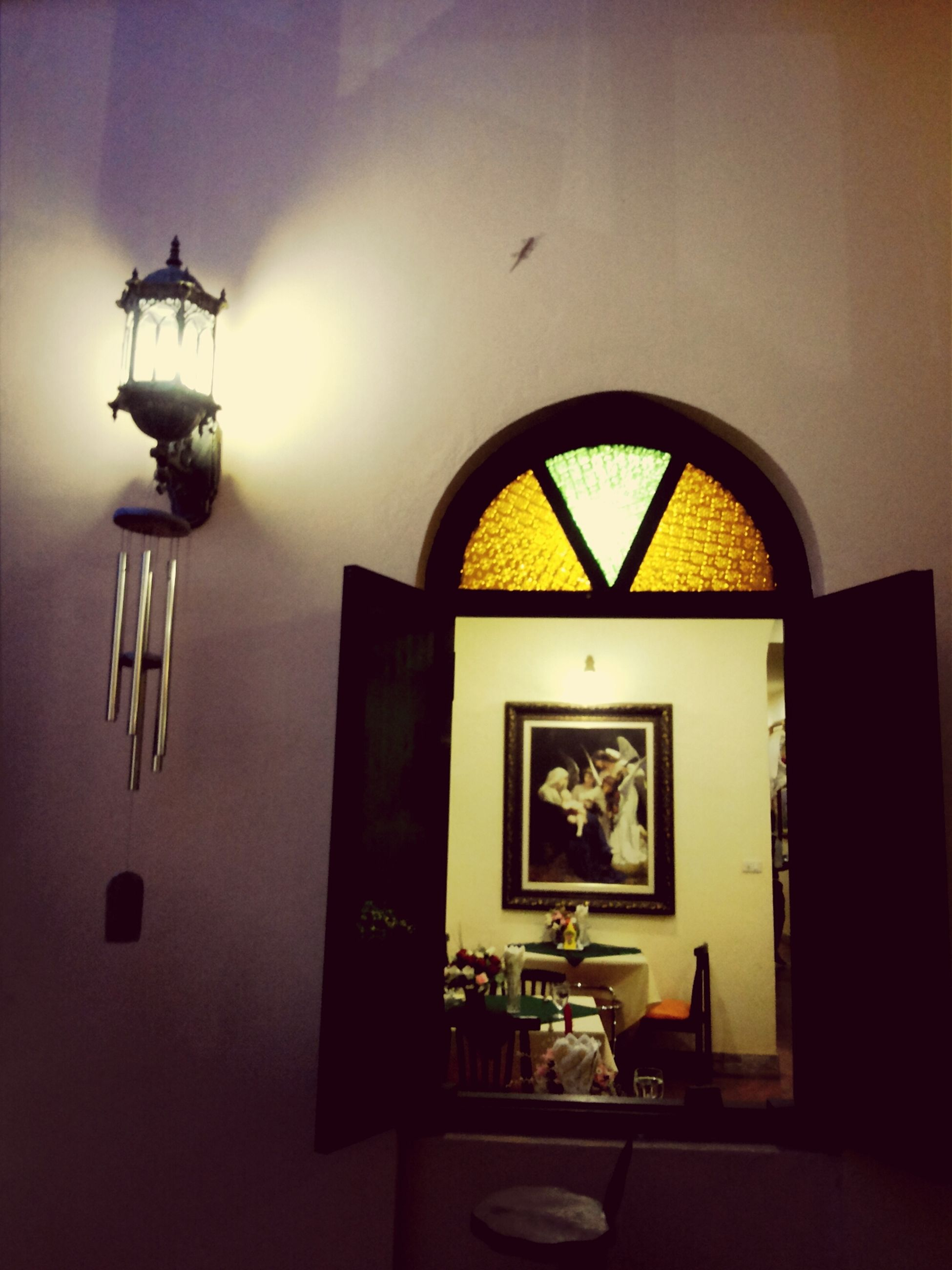 indoors, lighting equipment, electric lamp, illuminated, lamp, architecture, built structure, home interior, wall - building feature, hanging, window, lantern, low angle view, no people, wall, ceiling, house, electric light, old-fashioned, table