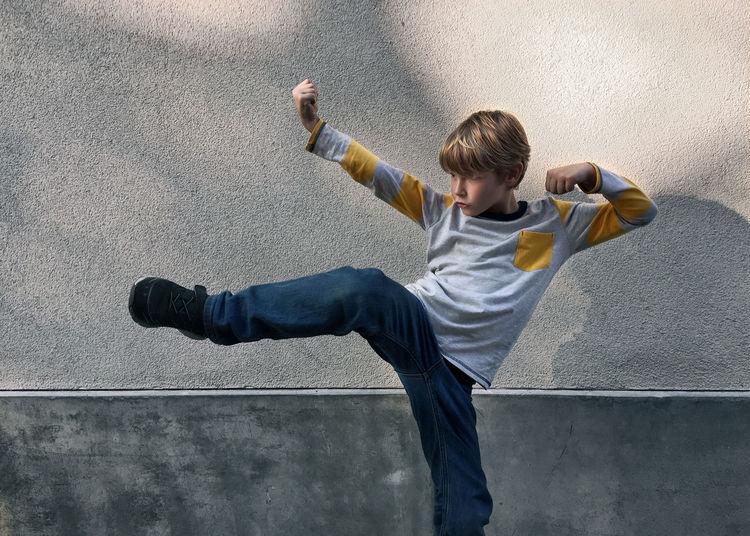 Boy Kicking By Gray Wall