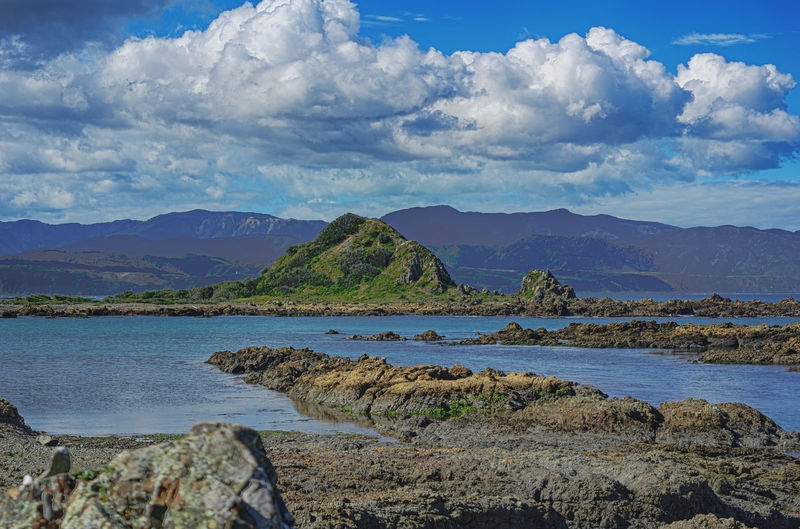 Scenic View Of Rocky Shore Against Cloudy Sky