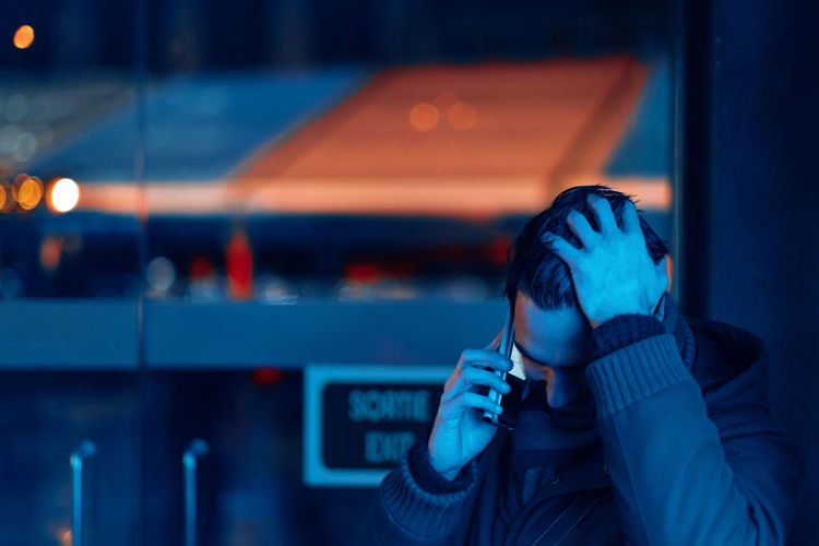 Man in a corner talking on the phone in an intimate conversation dipped in a blue neon light
