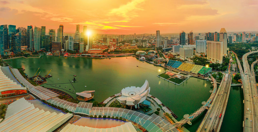 Panorama of Singapore Marina Bay with Financial District skyscrapers at sunset light reflected on the harbor. Roof top with Singapore skyline. Singapore cityscape aerial view. Singapore View Singapore City City Cityscape Skyline Marina Bay Sands Marina Bay Singapore Financial District  Skyscrapers Night Aerial View Night Lights Urban Bridge Modern Architecture Pedestrian Walkway Sea Seascape Waterfront Sunset Harbor Marina Marina Bay Panorama Rooftop Building Exterior Built Structure Architecture Water Sky Building Nautical Vessel Office Building Exterior Nature Transportation Skyscraper High Angle View Cloud - Sky Urban Skyline Landscape No People Outdoors Tall - High Modern Financial District
