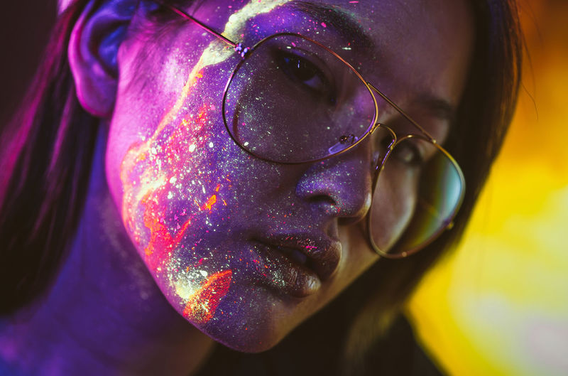 Beautiful young woman with face paint wearing eyeglasses