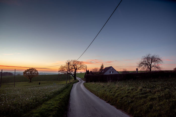 Sky Plant Sunset Road Tree Direction The Way Forward Transportation Nature Field Grass Landscape No People Land Environment Cable Diminishing Perspective Architecture House Scenics - Nature Outdoors